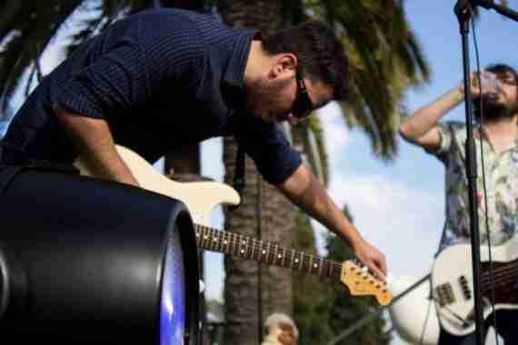 Jose Barroso, guitarra y vocalista en Delbosque. Al fondo, Carlos Almagro bebe de una botella de agua.